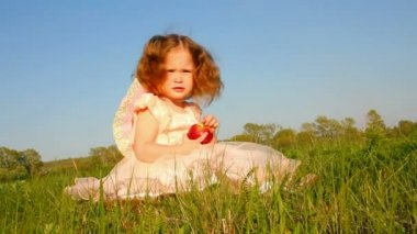 :Little girl eating apple on meadow — Stock Video