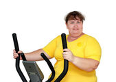 Overweight woman exercising on trainer — Stock Photo