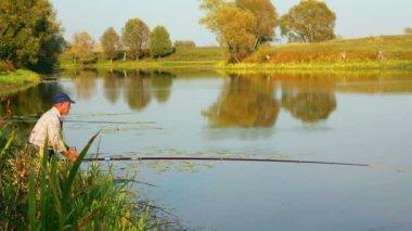Fishing senior on autumn lake — Stock Video