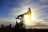 Werken oliepomp bij zonsondergang — Stockfoto
