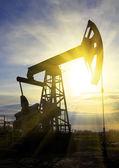 Pompe à huile travail au coucher du soleil — Photo
