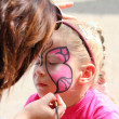 Artist paints on face of little girl — Stock Photo