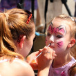 Artist paints on face of little girl — ストック写真