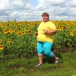 Overweight woman running along field of sunflowers — Stock Photo