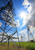 Tall electric masts against sun and sky — Stock Photo