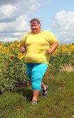 Overweight woman running along field of sunflowers — Stock Photo