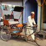 Old indian man rickshaw rolls his bike on street — Stock Photo #34165637
