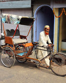 Old indian man rickshaw rolls his bike on street — Stock Photo