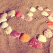 Heart symbol from shells on sand - vintage retro style — Stock Photo
