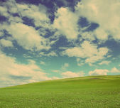 Green hill under cloudy sky - vintage retro style — Stock Photo
