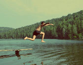 Boy jumping in lake - vintage retro style — Stock Photo
