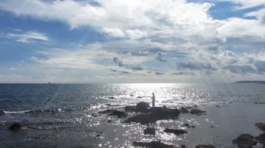 Fisherman with spinning near sea in sunlight — Stock Video