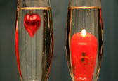 Heart and candle in glasses with champagne — Stock Photo