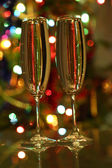 Glasses with champagne against festive lights — Stock Photo