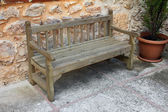 Old wooden bench near stone wall — 图库照片