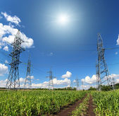 Electric masts and road in green field — Stock Photo
