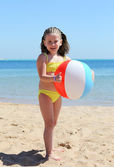 Happy little girl with ball on beach — Stock Photo