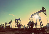 Oil pumps silhouette against sun - vintage retro style — Stock Photo