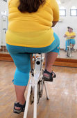 Overweight woman exercising on bike simulator — Stock Photo