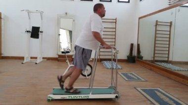 Overweight man running on trainer treadmill — Stock Video