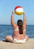 Overweight woman doing gymnastics on beach — Stock Photo