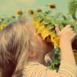 Little girl smelling sunflower - vintage retro style — Stock Photo
