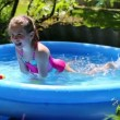 Girl in inflatable pool in  garden — Stock Video #50599989