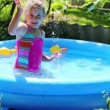 Girl in inflatable pool in summer garden — Stock Video #50604293