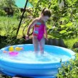 Girl in inflatable pool in summer garden — Stock Video #50605159