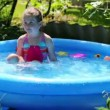 Girl in inflatable pool in summer garden — Stock Video #50605837