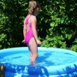 Girl in inflatable pool in summer garden — Stock Video #50608937