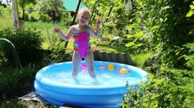 Girl in inflatable pool in summer garden — Stock Video