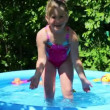 Girl in inflatable pool in summer garden — Stock Video #50610101