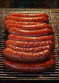 Traditional fresh sausages grilled on wire rack — Stock Photo