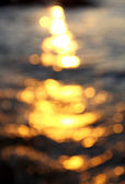 Out of focus bokeh background of sea water with sun reflections — Photo