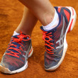 Tennis player legs on the clay court - Stock Photo