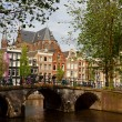 Amsterdam canals with bridge and typical dutch houses — Stock Photo