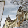 Buildings at the street reflecting in a puddle after rain — Stockfoto