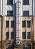Facade of building with giant outdoor thermometer — Stock Photo