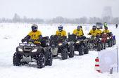 Passeios de moto-quatro motoristas sobre pista de neve — Fotografia Stock