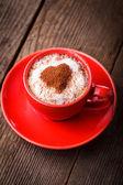 Czerwony kubek z kawą cappuccino — Zdjęcie stockowe