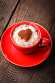 Red cup with cappuccino — Stok fotoğraf