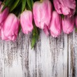 Pink tulips over wooden table — Stock Photo #22749049