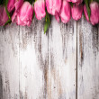 Pink tulips over wooden table — Stock Photo #22749111