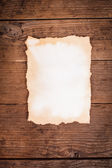 Aged paper on wood — Stock Photo