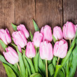 Pink tulips over wooden table - Stock Photo