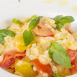 Photo of delicious risotto dish with herbs and tomato on white b — Stock Photo #12341100