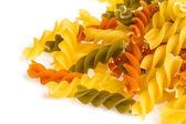 Uncooked pasta fusilli in different colours, white background — Stock Photo