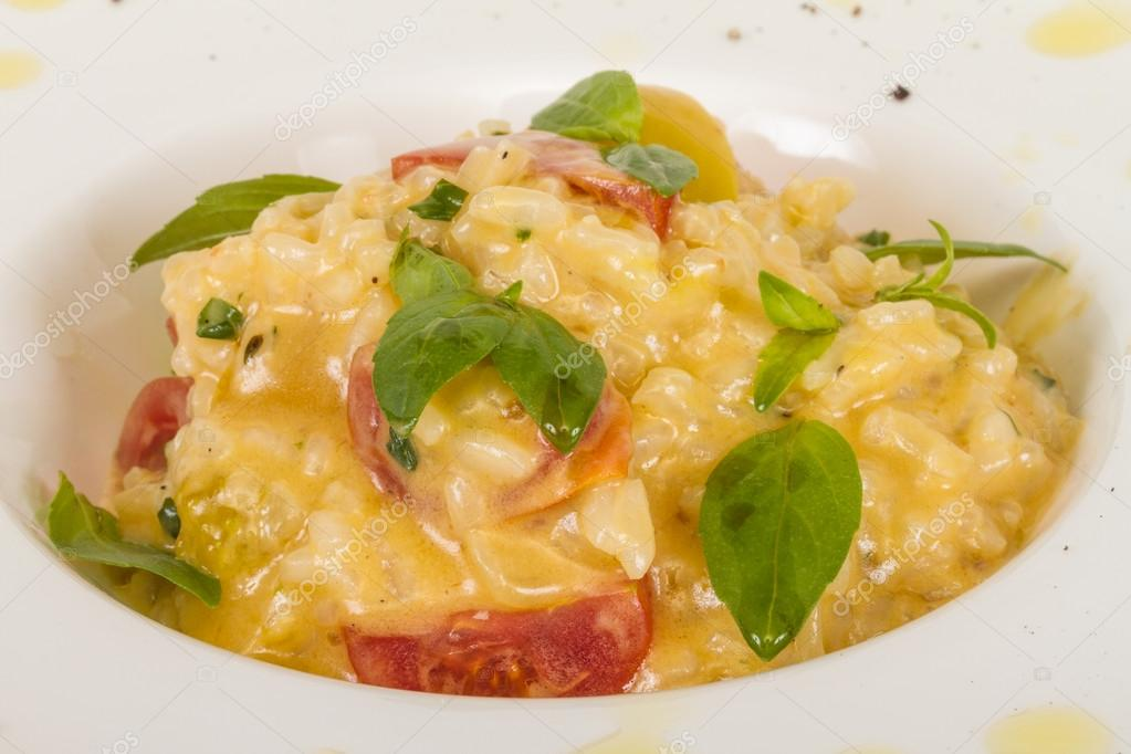 Photo of delicious risotto dish with herbs and tomato on white background — Stock Photo #13647827