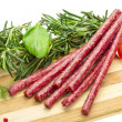 Salami with rosemary, basil and tomato — Stock Photo